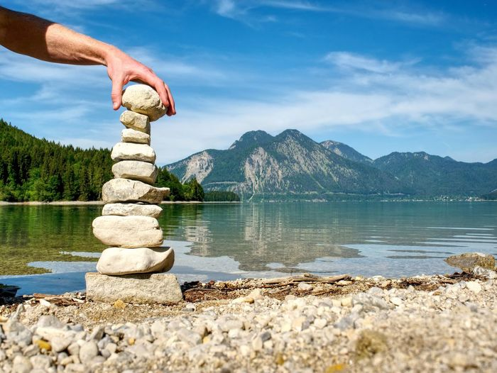 Stack of pebbles on rock by lake against sky