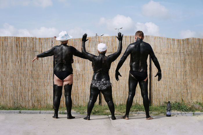 Rear view of friends covered with mud while standing at beach