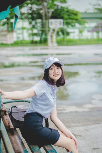 pretty girl collegian Casual Clothing Day Focus On Foreground Front View Leisure Activity Lifestyles Looking At Camera One Person Portrait Real People Sitting Smiling Three Quarter Length Water Women Young Adult Young Women