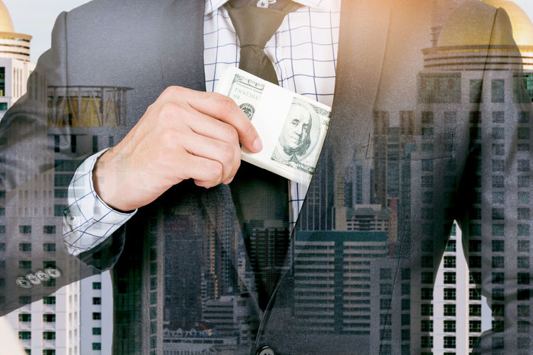 Double exposure of businessman with paper currency against cityscape