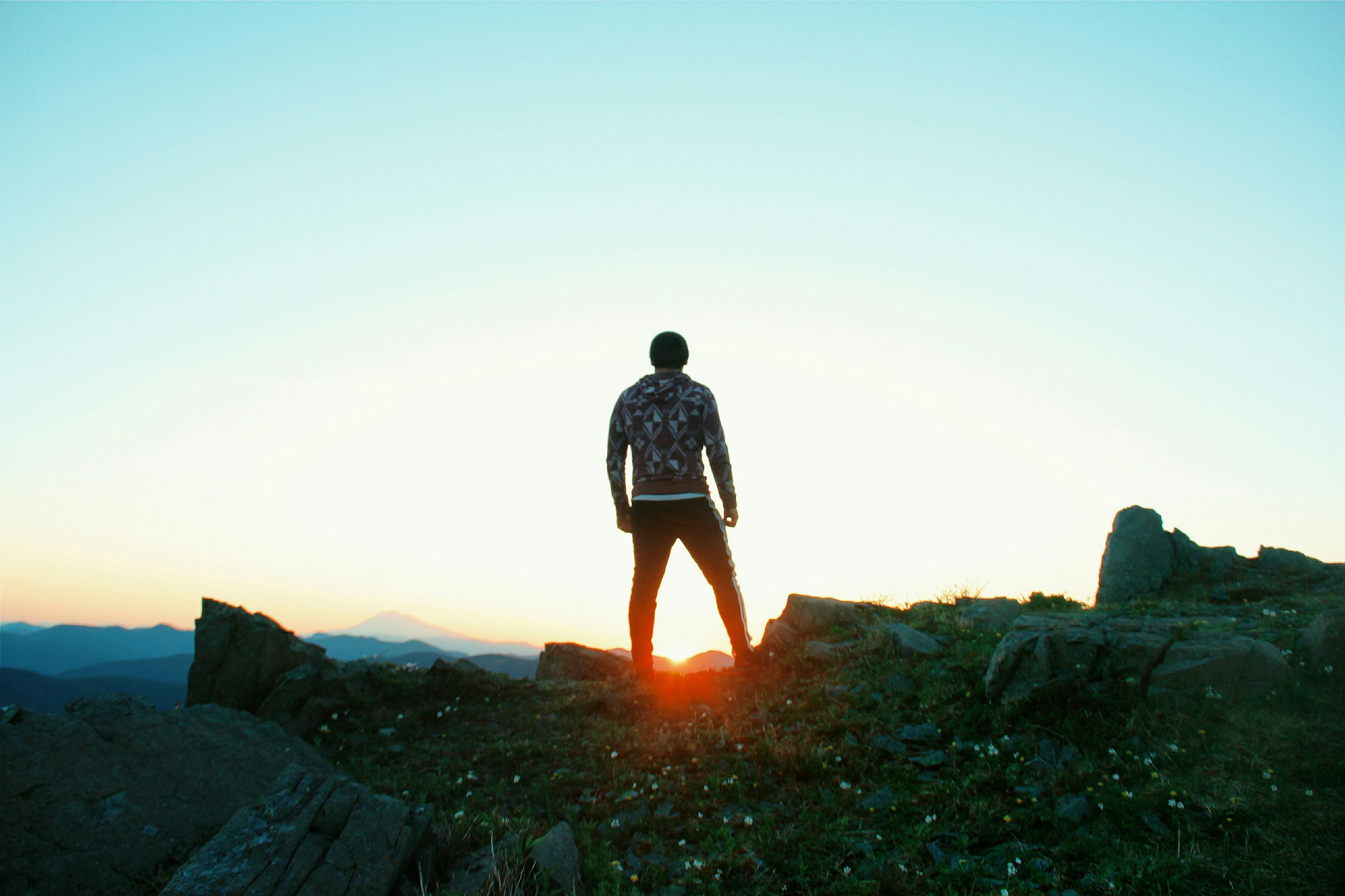 clear sky, copy space, standing, rear view, lifestyles, full length, leisure activity, men, tranquility, rock - object, tranquil scene, beauty in nature, nature, scenics, landscape, casual clothing, person, getting away from it all