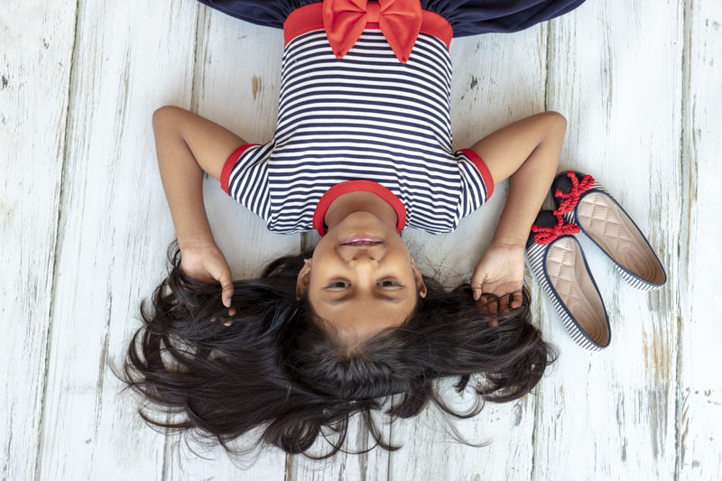 Beautiful brunette girl with striped dress next to her slippers One Person Lying Down Real People Leisure Activity Young Adult Front View Lying On Back High Angle View Portrait Young Women Relaxation Lifestyles Women Looking At Camera Directly Above Striped Adult Beautiful Woman Casual Clothing Hairstyle Hands Behind Head