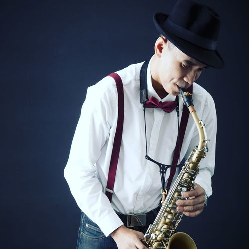 Musician Playing Saxophone While Standing Against Black Background