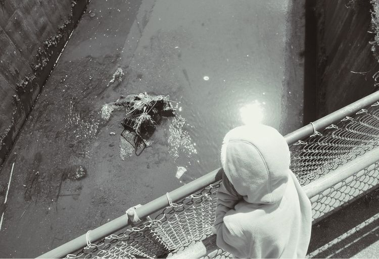 High Angle View Of Girl Looking At Canal From Footbridge
