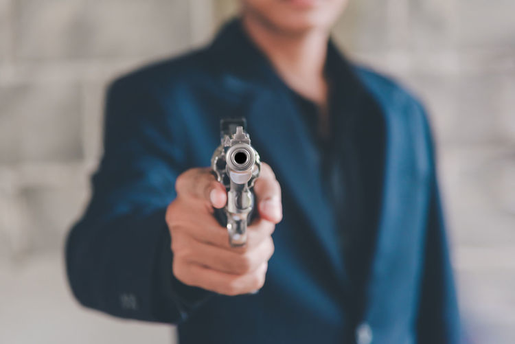 Midsection of man holding gun while standing against wall