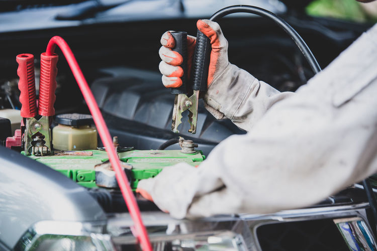 Mechanic repairing car engine in garage