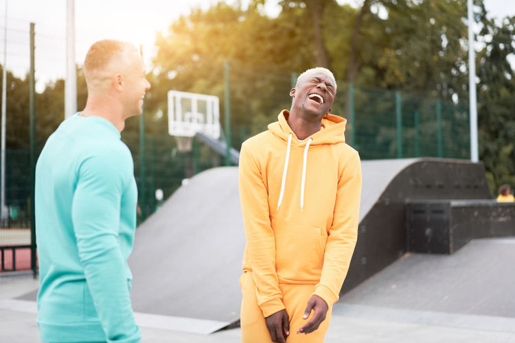 Cheerful friends laughing while standing outdoors