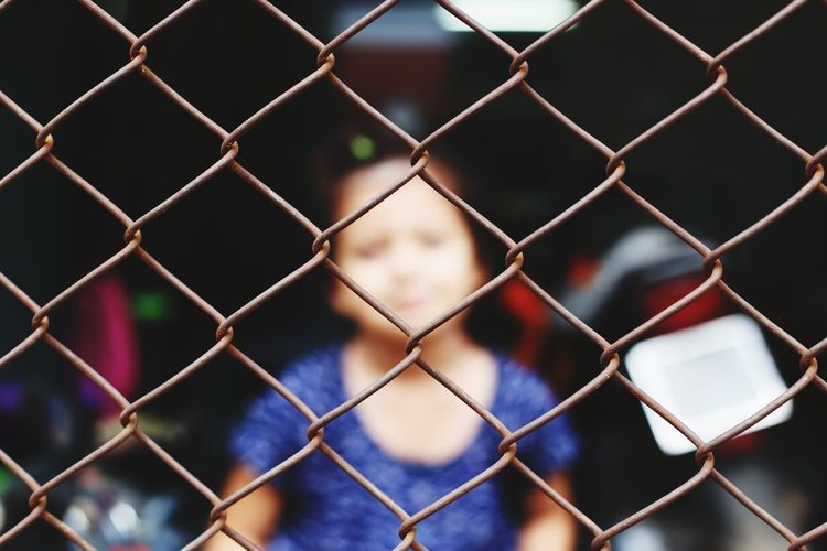 Girl seen through chainlink fence