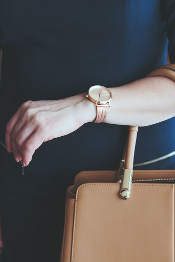 Midsection Of Woman In Dress Wearing Wristwatch While Holding Bag