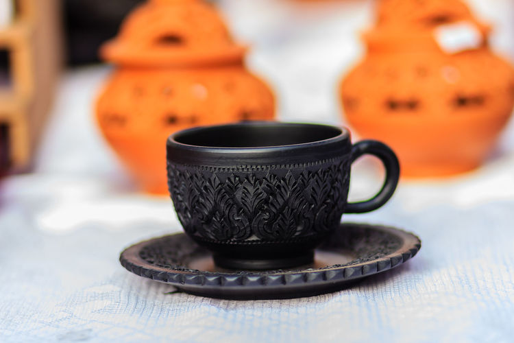 Beautiful Black Vintage Thai's style porcelain teacup, coffee cup hand made. Set of Black coffee cup with black plate in Thai's style pattern carving. Pattern Pieces Pattern, Texture, Shape And Form Porcelain  TeaCup Thai's Style Black Black Coffee Cup Black Plate Close-up Coffee Cup Coffee Cup And Plate Coffee Cup And Saucer Coffee Cupping Coffee Cups Day Earthware Focus On Foreground Food And Drink Freshness Hand Made Indoors  No People Orange Color Pattern Pattern Design Patterns & Textures Porcelain Bowl Porcelain Cup Pumpkin Table Tea Cup Teacups