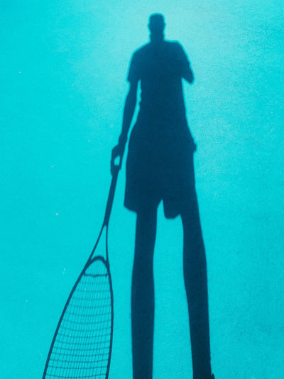 Shadow of person on blue sea