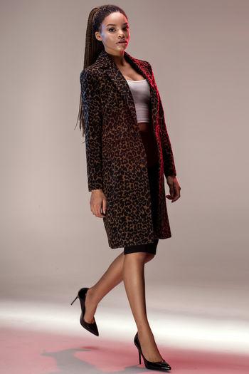 Portrait of female model walking against gray background