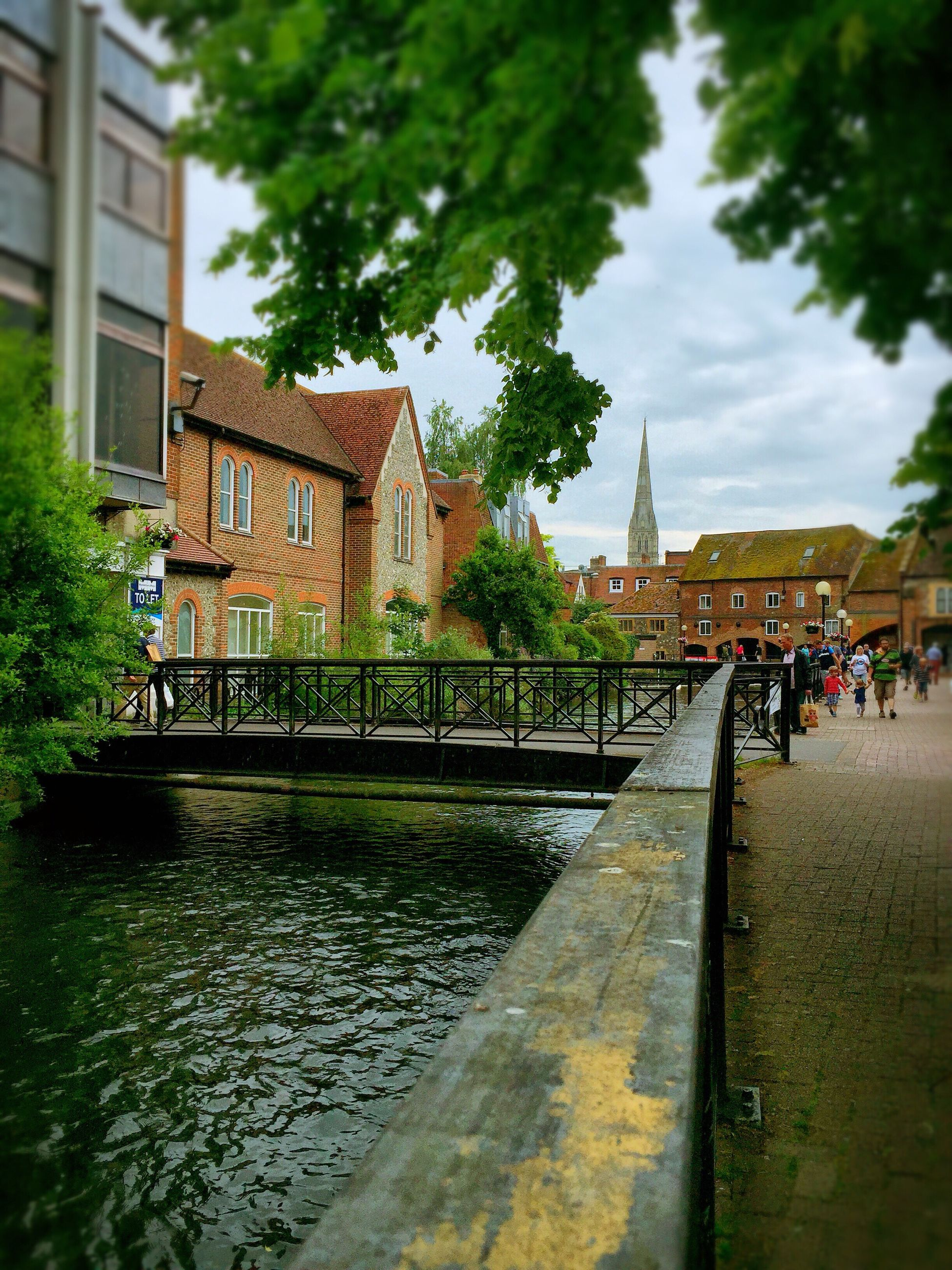 architecture, built structure, building exterior, water, large group of people, tree, sky, person, men, lifestyles, leisure activity, railing, incidental people, city, walking, river, day, bridge - man made structure, cloud - sky