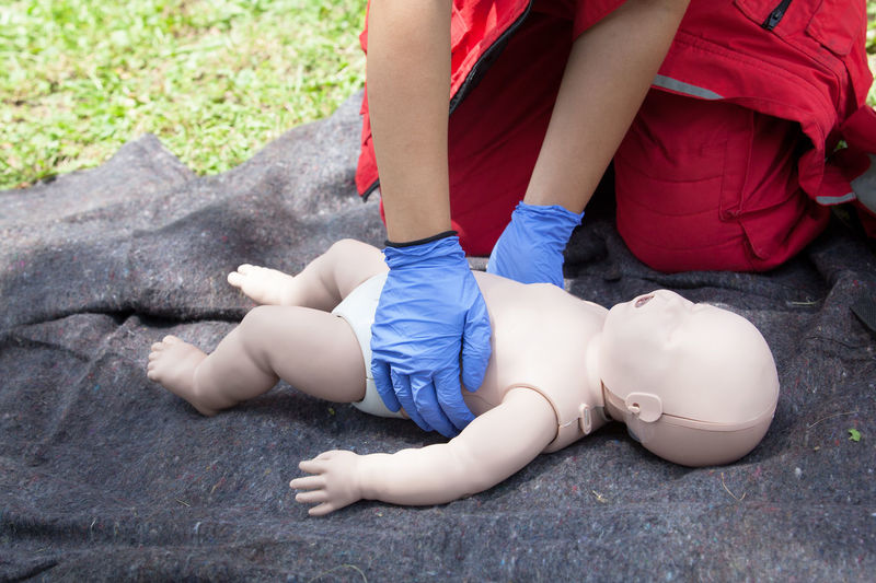 Midsection of person holding baby mannequin lying on grass field