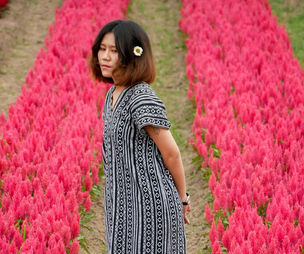 Full length of woman standing by pink flowering plants