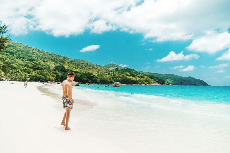 Shirtless man walking at beach against sky