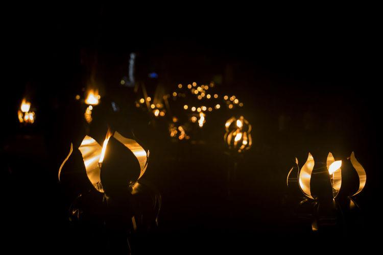 Close-up of illuminated lights in dark at night