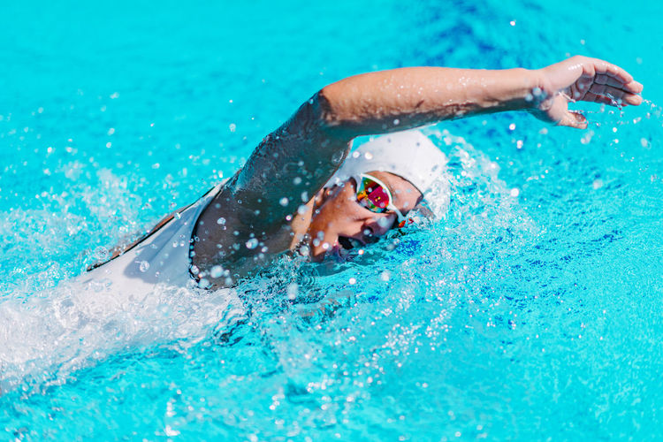 Female Swimmer on Training in the Swimming Pool Swimmer Female Water Sport Crawl Front Crawl Young Pool Competition Swimwear Athlete Goggles Training Swim Competitive Healthy People Active Cap Swimming Swimming Pool Energy Exercise Professional Woman Strength Adult Muscular Lifestyle Activity Race Action Winner Motion Health Skill  Caucasian White Exercising Healthy Lifestyle Sports Training Beautiful Outdoors Blue Sport Day One Person Turquoise Colored Swimming Cap