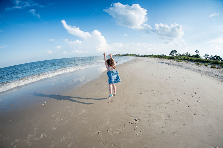 Rear view of girl jumping on beach against sky