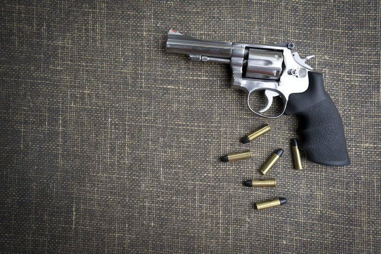 Directly Above Shot Of Pistol And Bullets On Table