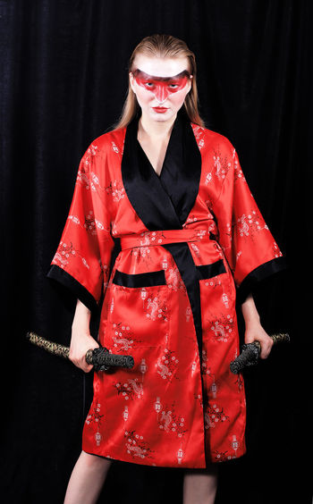 Portrait of young female model holding samurai swords while standing against black curtain