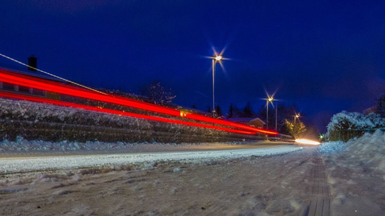 illuminated, night, light trail, speed, motion, long exposure, blurred motion, street, transportation, road, street light, traffic, winter, red, no people, car, snow, outdoors, cold temperature, high street, snowing, city, sky