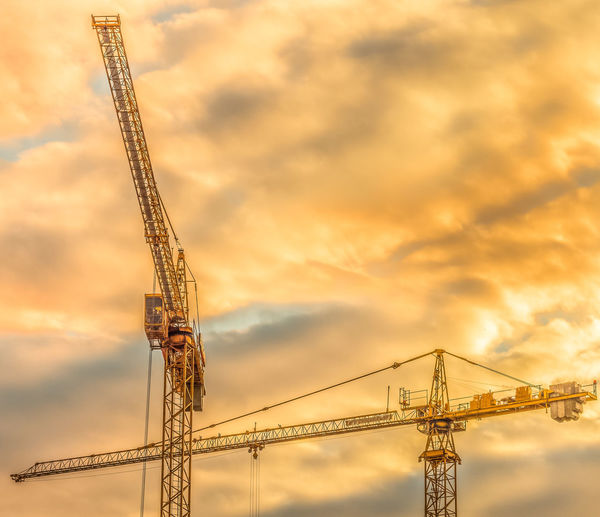 Low angle view of crane against sky at sunset