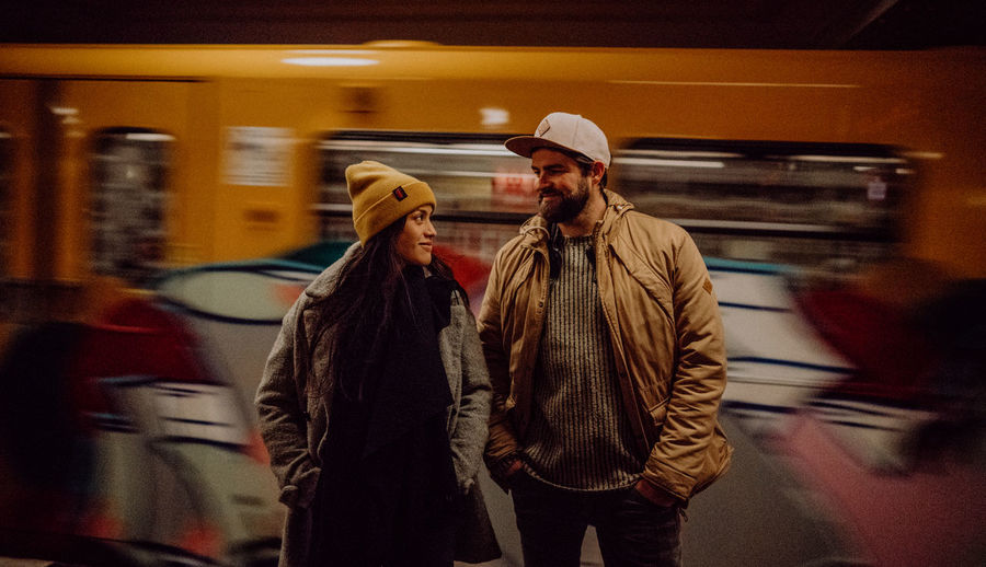 Couple standing by train at railroad station