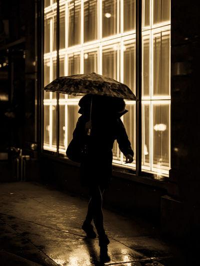 Full length of man standing on wet street at night