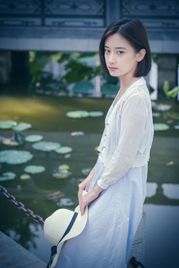A beautiful young woman sitting besides the lotus. One Person Women Real People Lifestyles Leisure Activity Young Adult Young Women Looking At Camera Three Quarter Length Focus On Foreground Casual Clothing Adult Standing Portrait Beautiful Woman Beauty Day Hair Hairstyle Outdoors Lotus Water Lily
