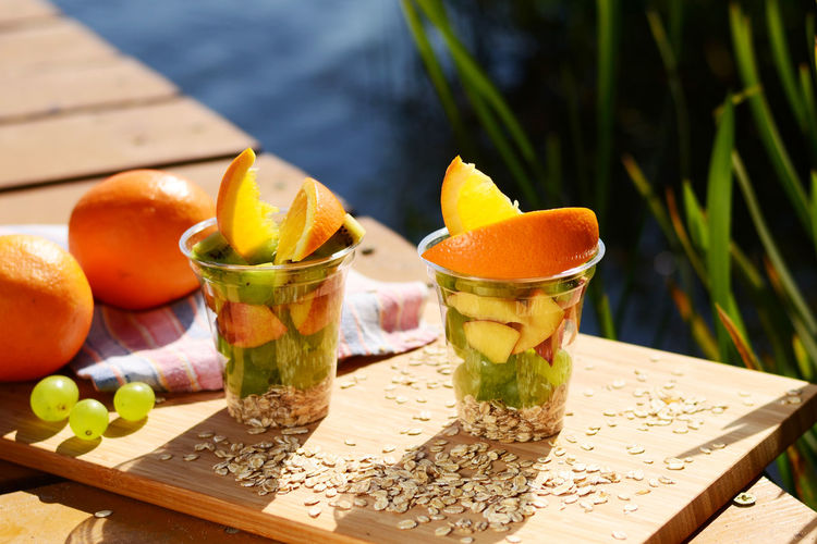 Fruits In Disposable Cups On Cutting Board Over Table
