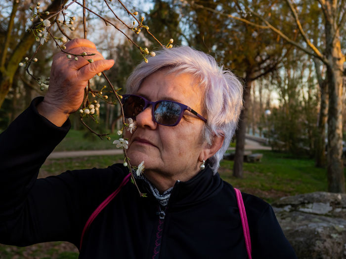 Close-up of senior woman smelling cherry blossoms