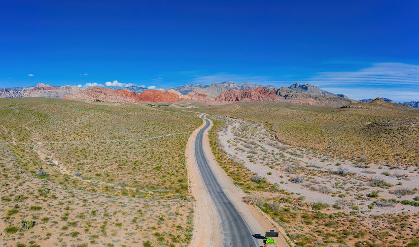 Panoramic view of road amidst desert against blue sky