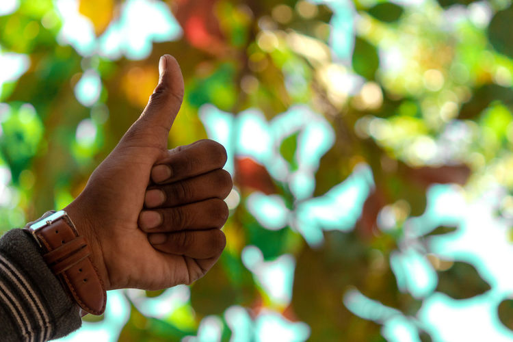Cropped hand of person gesturing thumbs up outdoors