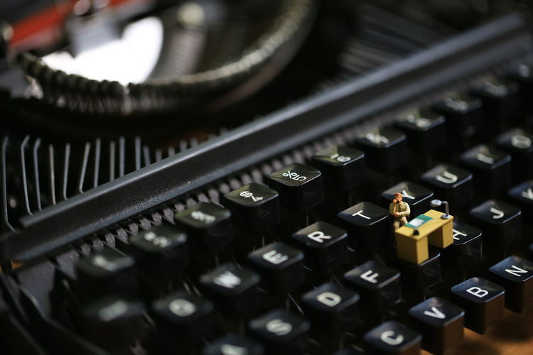 man busy on keyboard Typewriter Tiny Machinery Electrical Equipment No People Surreal Worker Working Desk Help Desk Office Technology Selective Focus Indoors  Retro Styled Busy Typography Keyboard
