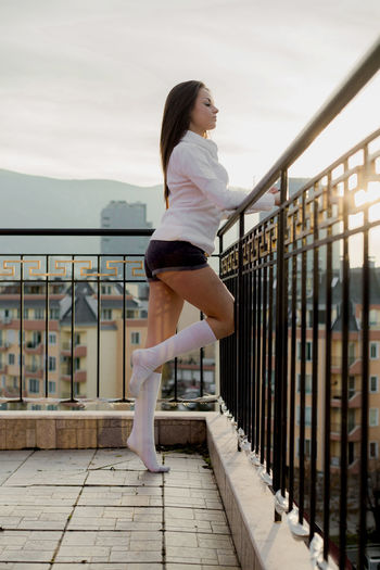 Young woman standing at balcony