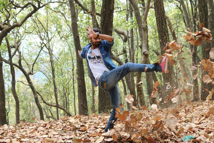 Man kicking dry leaves in forest
