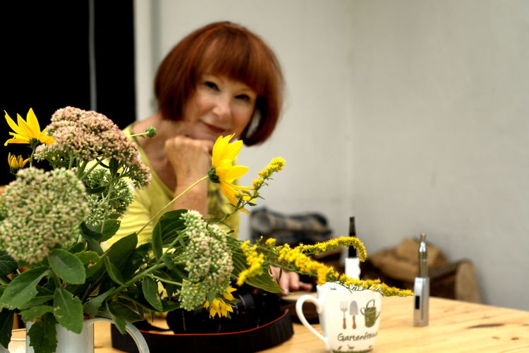 Portrait of woman by potted plant on table at home