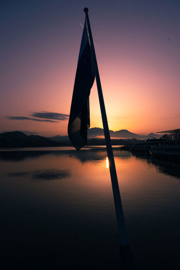 Silhouette pole by lake against sky during sunset