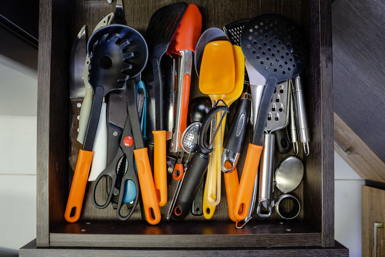 Mess in the cutlery drawer. top view of various kitchen utensils without organization.