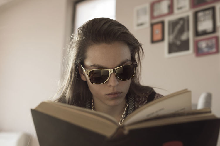 Woman wearing sunglasses while reading book