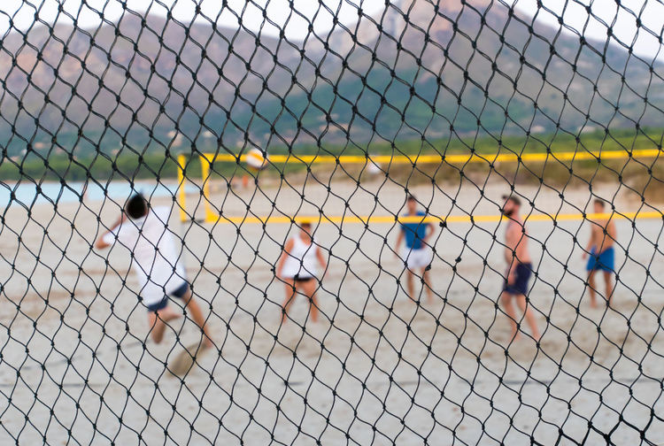 Friends playing volleyball at beach seen through fence