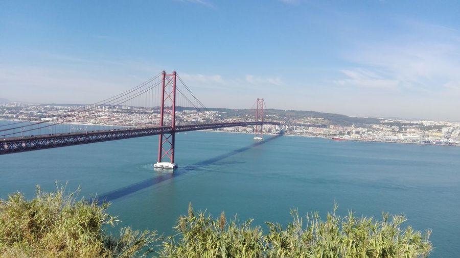Scenic view of 25 de abril bridge over tagus river against sky