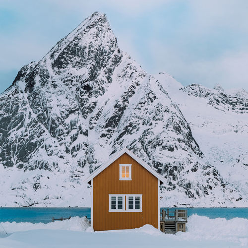 Snow covered house and mountain against sky