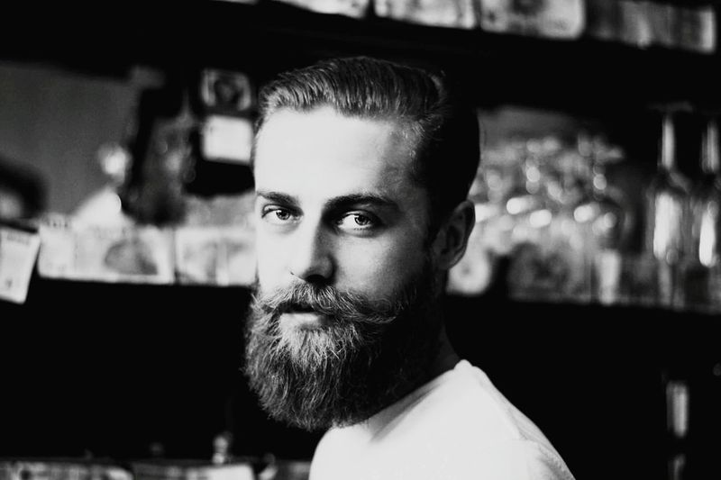 Close-up portrait of bearded man at bar