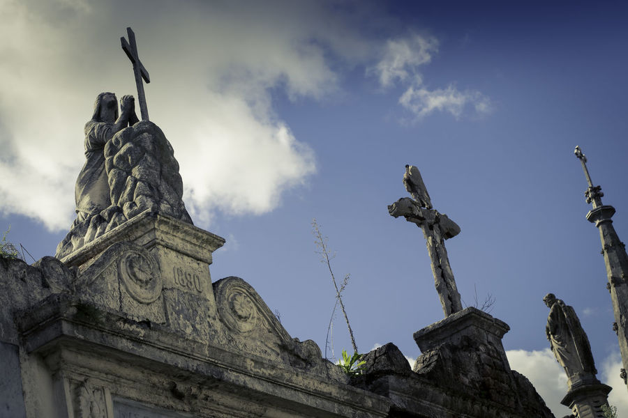 La Recoleta Cemetery, Buenos Aires, Argentina Upper class death in Argentina. The myriad of tombs and mausaleums open to the public housing the wealthy and famous of Argentine society. A macabre place of death and celebration. The Photojournalist - 2018 EyeEm Awards Angel Architecture Art And Craft Built Structure Cloud - Sky Craft Creativity Day History Human Representation Low Angle View Male Likeness Nature No People Outdoors Representation Sculpture Sky Statue The Past Travel Destinations
