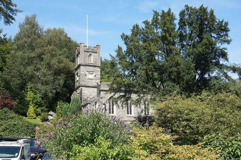 Beauty In Nature Blue Blue Sky Church Clock Day Green Green Color Growing Growth Low Angle View Lush Foliage Nature No People Old Old Buildings Outdoors Plant Sky Sunny Tranquility 5861 Trees Trees And Sky Windows