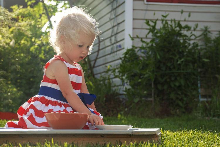 Cute girl sitting in yard