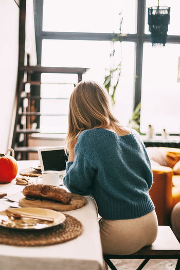 A blonde girl works in the morning at a laptop and drinks coffee. work online, freelance,