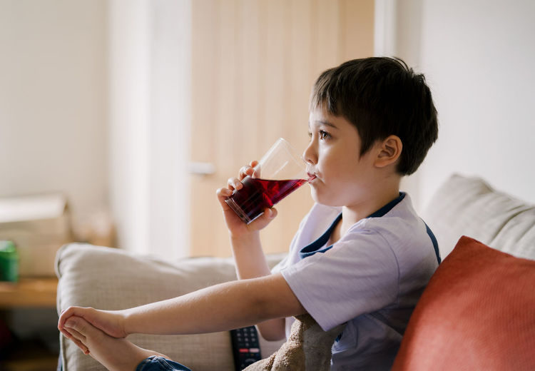 Side view of boy drinking at home